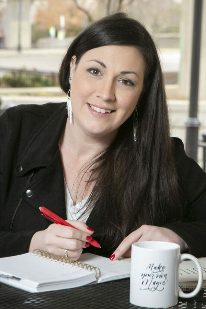 Amber Brooks sitting with journal and coffee cup